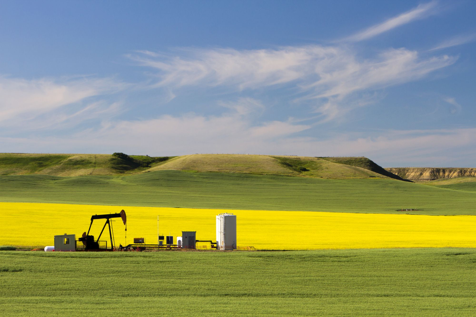 An oil pumpjack near Drumheller, Alberta, Canada. An oil pumjack is the the overground drive for a reciprocating piston pump in an oil well. It is used to mechanically lift liquid out of the well if not enough bottom hole pressure exists for the liquid to flow all the way to the surface.